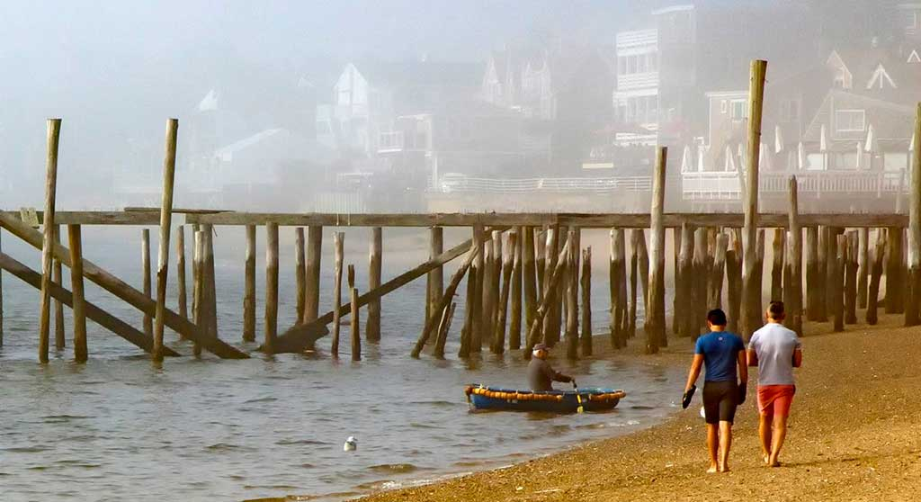 Fall in Provincetown, book now for Fall and Winter, two guys walking on the beach on a foggy morning