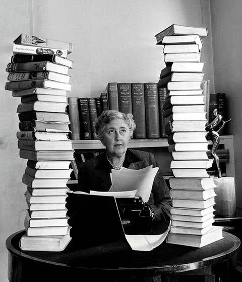 Black and White photograph of Agatha Christie with her stacks of books