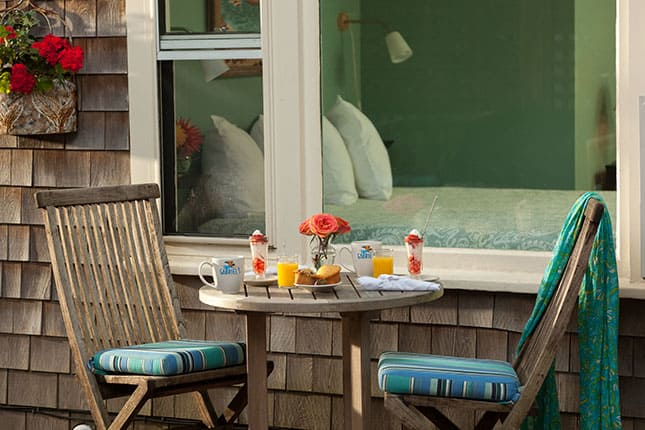 Breakfast table set for two with orange juice and smoothies outside Grace in our Provincetown Hotel